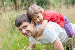Daddy carrying little girl on his back Stock Photos