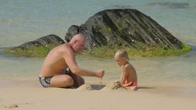 Daddy and cute boy build with wet sand on ocean beach. Happy daddy and cute little boy build with wet sand on ocean beach at large rock on sunny day slow motion stock video