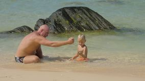 Daddy and cute boy play with wet sand resting on surf line