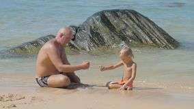 Daddy and cute boy sit on surf line playing with wet sand