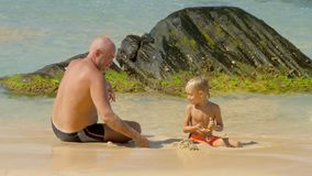 Daddy and cute son throw wet sand playing in water on beach