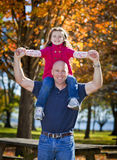Daddy and daughter. Daddy carrying daughter on shoulders in the fall royalty free stock images