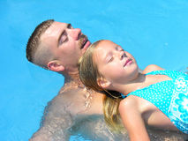 Daddy and daughter. A young girl and her father relaxing in the swimming pool Royalty Free Stock Photos