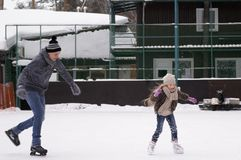 Daddy and daughter skate on the rink under the open sky on a winter day royalty free stock photography