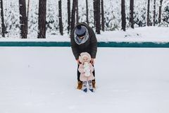 Daddy and daughter walking with snow-covered pine forest royalty free stock images