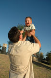Daddy Day. Father throws baby boy in the air and catches him. A view from the ground of a happy baby with his daddy. Against a blue sky Royalty Free Stock Photography