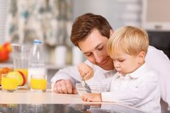 Daddy encourages his son to finish a cereal royalty free stock image