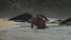Daddy has fun carrying little boy on back in sea at beach