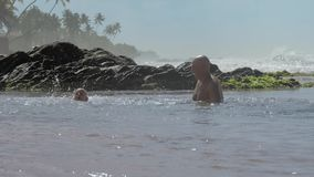 Daddy has fun with little son in warm sea water on sunny day