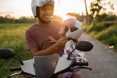 Daddy help her daughter to fasten the helmet royalty free stock image