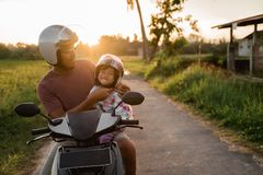Daddy help her daughter to fasten the helmet stock photo