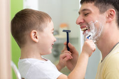 Daddy and his child shaving and having fun in. Daddy and his child son shaving and having fun in bathroom Royalty Free Stock Image