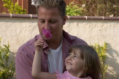 A daddy and his daughter. A handsome man holds his cute daughter while she shows him a flower stock photos