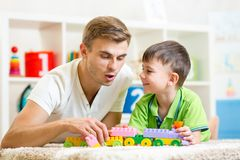 Daddy with his kid son play together. Daddy with his kid son playing together Royalty Free Stock Images