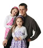 Daddy and his little girls. Handsome father and two cute young daughters dressed up Royalty Free Stock Image