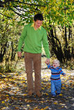 Daddy and his little son. Walking through the park in autumn Royalty Free Stock Photography