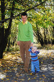 Daddy and his little son. Walking through the park in autumn Royalty Free Stock Photo