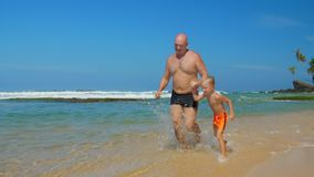 Daddy holds hand of little boy running along ocean beach