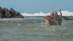 Daddy holds son on shoulder splashing water in warm ocean