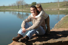 Daddy Hug. A dad sits on a rock by a pond as his daughter comes up behind him. Father and daughter at the park. Little girl hugs her dad royalty free stock photo