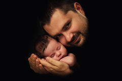 Daddy hugs his newborn baby. Father's love. Close-up portrait on a black background.  royalty free stock photography