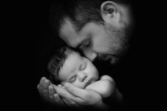 Daddy Hugs His Newborn Baby. Father `s Love. Close-up Portrait On A Black Background Stock Images
