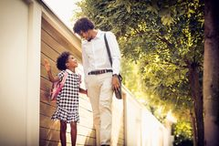 Daddy i have funny day in school. African American daughter and her father walking trough city park and talking stock photos