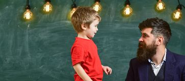 Daddy and kid staring at each other. Adult male and small boy side view over green background with bright light bulbs.  Royalty Free Stock Photos