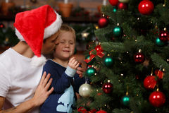 Daddy kisses son at tree. Daddy kisses his son at Christmas tree Royalty Free Stock Photography