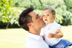 Daddy kissing baby. Young daddy kissing baby girl outdoors stock image