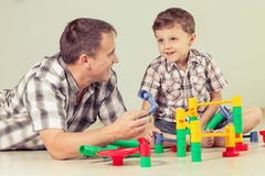 Daddy with little boy playing with toy  on the floor at the day Royalty Free Stock Photo