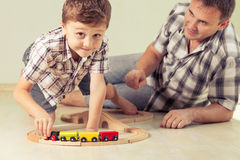 Daddy with little boy playing with toy train on the floor at the Stock Photos