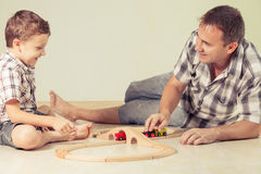 Daddy with little boy playing with toy train on the floor at the Royalty Free Stock Images