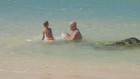 Daddy and little son swim in azure ocean on sunny day