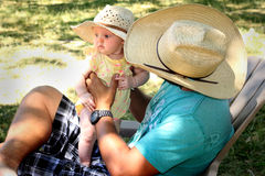 Daddy Looking at Newborn. A side view of a cute newborn baby wearing a straw hat being held by Cowboy Daddy. Shallow depth of field Royalty Free Stock Photos