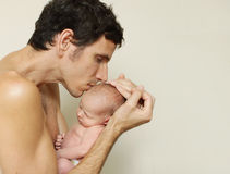 Daddy love. Daddy lovingly kissing newborn baby on the head Stock Images