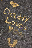 Daddy loves you statement. The statement DADDY LOVES YOU written on stone with golden paint Stock Images