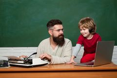 Daddy play with schoolboy. Daddy Teacher. Teacher and schoolboy using laptop in class. Man teaches child. Concept of. Education and teaching. father teaching royalty free stock photography
