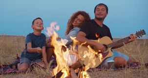 Daddy plays guitar , mom with son enjoy while relaxing on family picnic near bonfire. close-up. Daddy plays guitar , mom with son enjoy while relaxing on family stock footage
