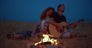 Daddy plays guitar , mom with son enjoy while relaxing on family picnic near bonfire. close-up.