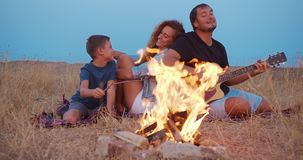 Daddy plays guitar , mom with son enjoy while relaxing on family picnic near bonfire. close-up. stock footage