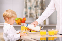 Daddy pours some milk into the bowl Royalty Free Stock Photo