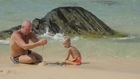 Daddy pours wet sand playing with cute son on beach