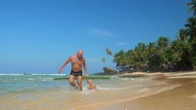 Daddy pulls boy by hand along tropical beach under blue sky