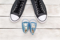 Daddy`s boots and baby`s shoes, fathers day concept. Flat lay stock image