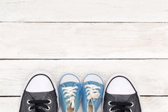 Daddy`s boots and baby`s sneakers, on white wooden background, f Royalty Free Stock Images