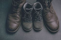 Daddy's boots and baby's shoes, fathers day concept. Fathers day concept. Big and small shoes stock photo