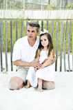 Daddy's Girl Too. Beautiful little girl sitting on her daddy's knee by a wooden fence in the sand along the shore Royalty Free Stock Photos