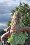 Daddy's Got Me. Little girl riding on her daddy's shoulders Royalty Free Stock Photography