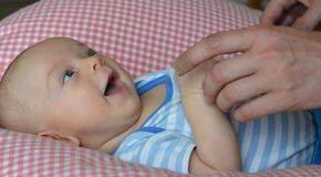 Daddy´s hands are playing with his newborn son. Royalty Free Stock Photography